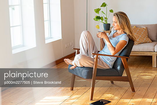 Woman in loungewear having coffee at home - p300m2277505 by Steve Brookland
