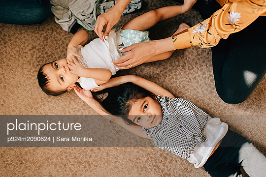Girl lying on nursery floor while mother changing baby brother's diaper, overhead portrait - p924m2090624 by Sara Monika