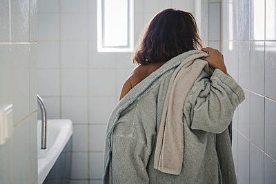 Woman putting on bathrobe - p1150m2125984 by Elise Ortiou Campion