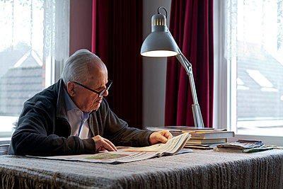 Senior man reading newspaper - p265m1573935 by Oote Boe