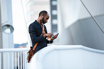 Young businessman with earphones and coffee to go using smartphone outdoors - p300m2160668 von Josep Suria