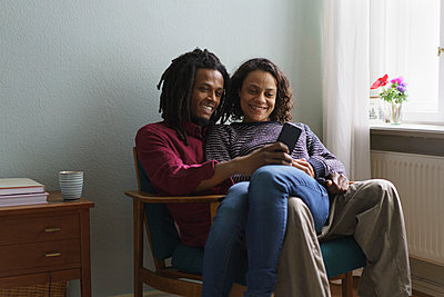 Smiling multi-ethnic couple using smart phone while sitting on armchair at home - p301m1406344 by Halfdark