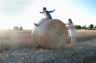 Girls playing on hay bale in field - p42916834f by Simon Potter