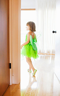 Child in room with green fairy costume - p429m819579 by Angela Bird