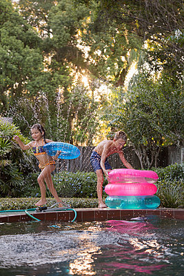 Young girl, running with inflatable ring beside outdoor swimming pool, boy stacking leftover rings - p924m1493692 by Kinzie Riehm