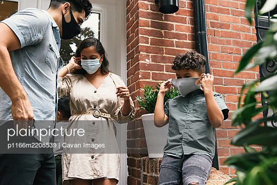 Family and young son putting on masks to go out of brownstone home - p1166m2208539 by Cavan Images