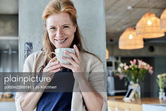 Smiling mature woman holding coffee cup against column at home - p300m2265191 by Jo Kirchherr