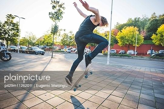 Young male urban skateboarder doing skateboarding jump trick on sidewalk