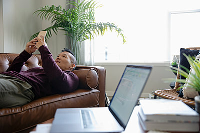 Man relaxing on sofa with smart phone, taking a break from work - p1192m2088547 by Hero Images