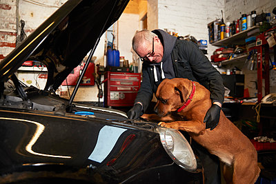 Male mechanic repairing car while looking at dog in garage - p300m2276174 by Pete Muller