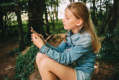 Side view of blond girl using smart phone in forest - p426m1543044 by Maskot