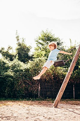 Side view of boy in mid air jumping from swing, Ulm, Baden Wuerttemberg, Germany - p429m1105639 by JFCreatives