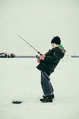 A young boy ice fishing and gets a bite while ice fishing at Wabamun Lake; Wabamun, Alberta, Canada - p442m2074103 by LJM Photo