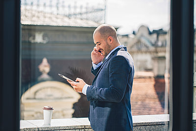 Caucasian businessman talking on cell phone at window - p555m1414278 by Lumina Images