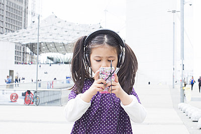 Girl looking at smartphone and listening to headphones outdoors - p623m1487524 by Anne-Sophie Bost