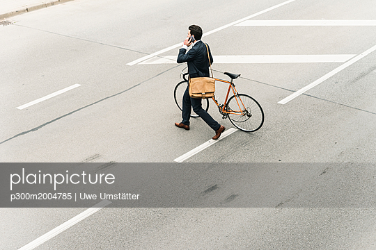 Businessman with bicycle on cell phone walking on the street - p300m2004785 von Uwe Umstätter