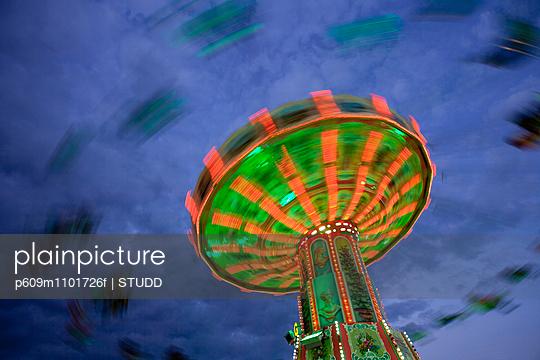 Low angle view of people enjoying carousel ride at Oktoberfest - p609m1101726f by STUDD