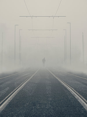 Man walking on tram tracks in fog - p1280m2151519 by Dave Wall