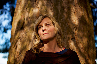Portrait serene woman standing at sunny tree trunk - p301m2148956 by Nik West