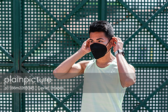 Portrait of Latin American athlete putting on a face mask. - p1166m2269345 by Cavan Images