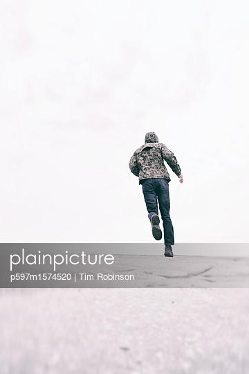 Man in hoody running away - p597m1574520 by Tim Robinson