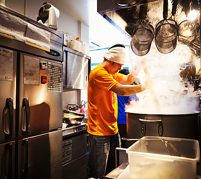 The ramen noodle shop, staff preparing food. Two men stirring a vat of noodles.  - p1100m1185660 by Mint Images