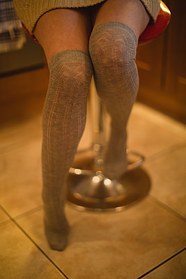Woman sitting on a stool in kitchen - p1315m1421828 by Wavebreak
