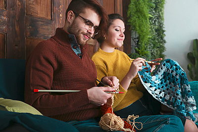 Young couple knitting and crocheting in living room - p300m1505430 by Retales Botijero