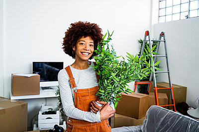 Happy afro woman holding potted plant during relocation in new apartment - p300m2251474 by Giorgio Fochesato