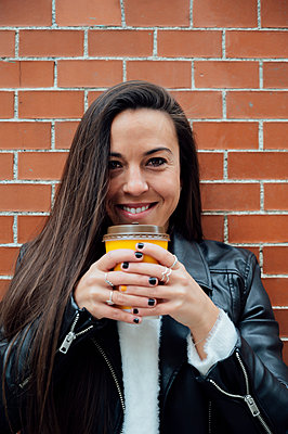 Smiling woman in leather jacket holding reusable cup against brick wall - p300m2267121 by Miguel Angel Partido Garcia