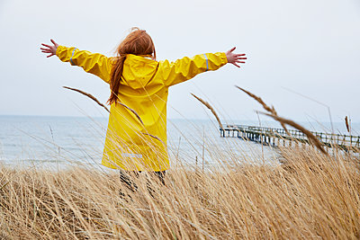 Girl in yellow raincoat standing at sea - p312m1495854 by Lina Arvidsson