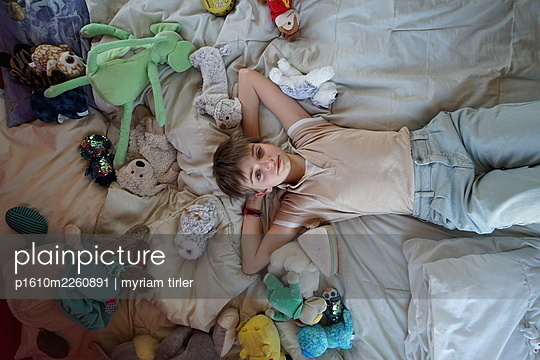 A little girl on her bed full of cuddly toy - p1610m2260891 by myriam tirler