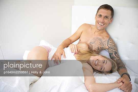 Couple in love embracing in bed - p1640m2259597 by Holly & John