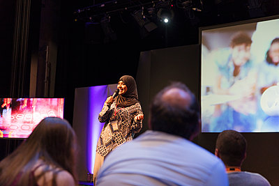 Smiling female speaker in hijab talking with microphone on stage - p1023m2187599 by Sam Edwards