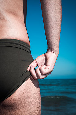 Man adjusting his swim briefs on the beach - p1423m2109224 by JUAN MOYANO