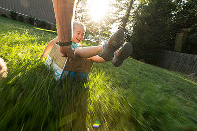 Father pulling daughter across grass in cardboard car - p1480m2229497 by Brian W. Downs