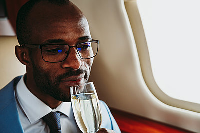 Businessman drinking champagne in private jet - p300m2256378 by OneInchPunch
