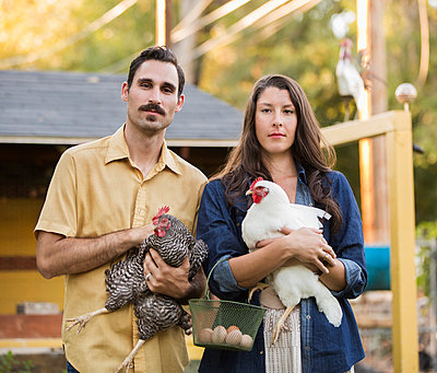 Couple holding chickens and eggs outside coop - p555m1420601 by Hill Street Studios