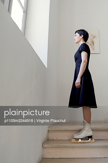 Woman in black dress and skates in the stairwell - p1105m2244918 by Virginie Plauchut