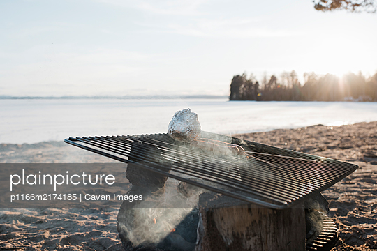food cooking on an outdoor fire at the beach at sunset in Sweden - p1166m2174185 by Cavan Images