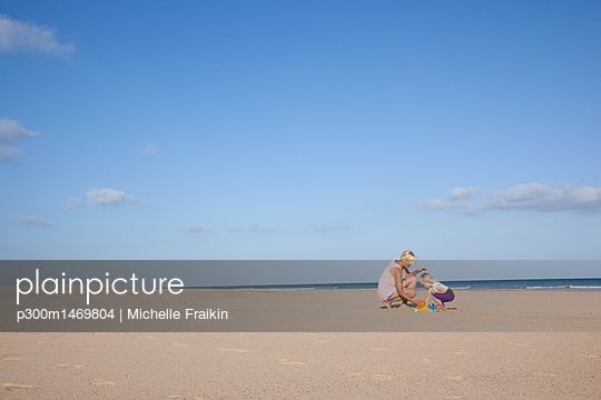 Spain, Fuerteventura, mother and daughter playing on the beach - p300m1469804 by Michelle Fraikin