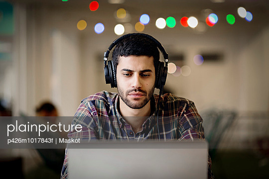 Businessman wearing headphones while working late on laptop in creative office