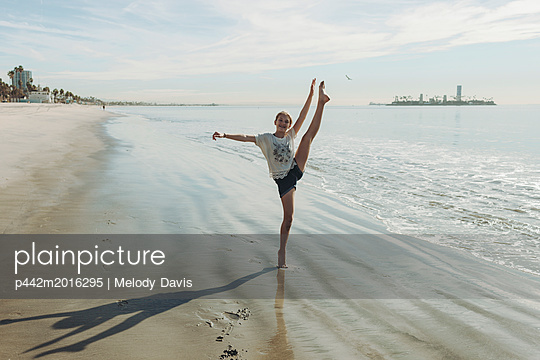 A girl in a dance pose at the beach; Long Beach, California, United States of America - p442m2016295 by Melody Davis