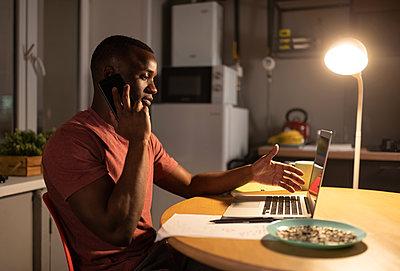 Black freelancer discussing data during phone conversation - p1166m2248864 by Cavan Images