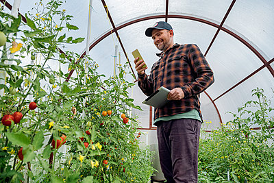Smiling man using mobile phone while standing green house - p300m2221542 by Konstantin Trubavin