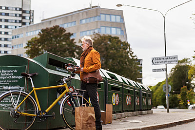 Man putting garbage into recycling bin - p312m2091637 by Pernille Tofte