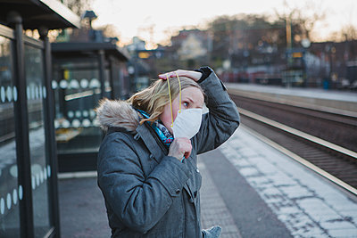 Woman wearing protective mask on train station platform - p312m2190994 by Madeleine Wejlerud
