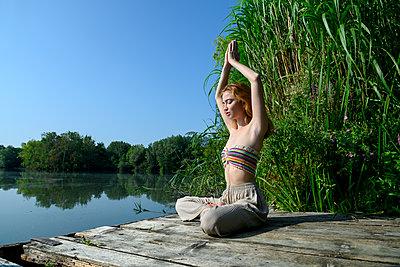 Junge Frau macht Yoga am See - p427m2209800 von Ralf Mohr