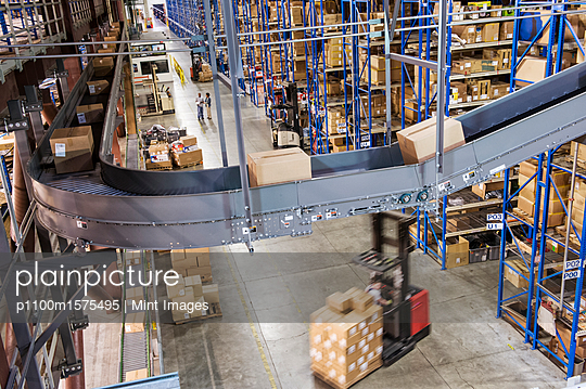 Overhead view looking down an aisle of large racks,  conveyor belts and fork lifts,  in a distribution warehouse of cardboard boxes holding products. - p1100m1575495 by Mint Images