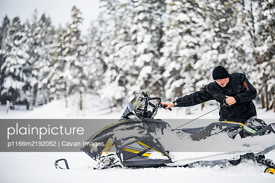 Senior man starting snowmobile with pull cord. - p1166m2192052 by Cavan Images